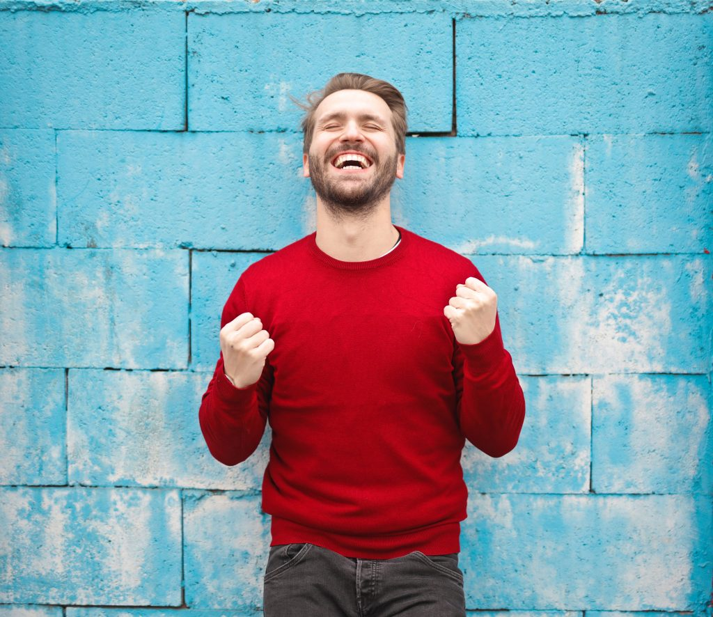 happy yes man standing against a blue wall